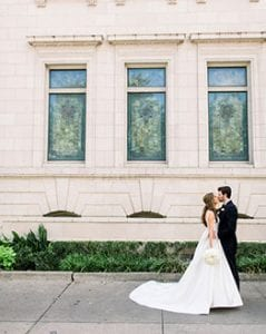 Bride in a cascading white gown and groom in his black tux standing in front of the church, kissing each other