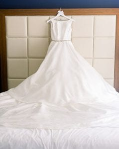 Wedding gown hanging on a white hanger on a bedframe