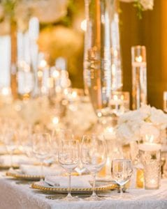 Glassware, flatware and plateware on a headtable, with tall centerpieces and low florals and silver votives up and down the head table