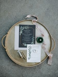 Black, white and green wedding invitation suite on a gold tray with blush ribbon and jewelry