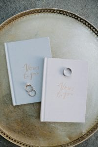 Blue and pink vow books in gold font, with wedding bands on a gold tray