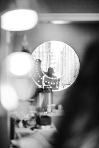Reflection of the bride and makeup artist in a circle mirror