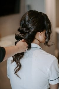 Womans hair being braided as she sits in a white pajamas set