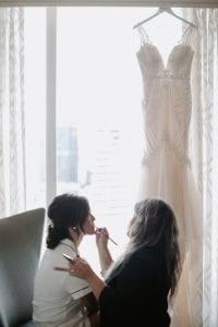 Bride getting her makeup done, while her dress hangs in by the window