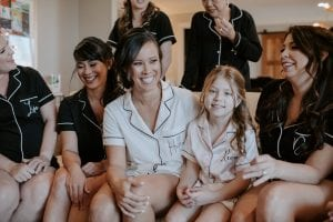 Bride and her bridesmaids in matching pajamas of black and white, with the flower girl waiting while getting ready