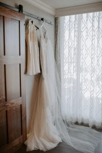 Wedding dress and flower girl dress hanging on a wall by a window