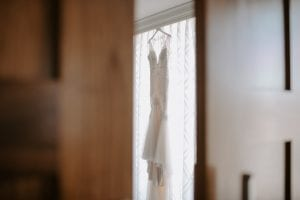 White wedding gown hanging on a hanger, by a window with white drapes