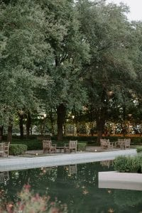 A view of the gardens in Marie Gabrielle, with a pond, and wooden chairs