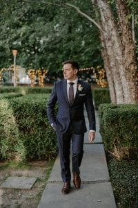 Groom walking in the gardens of Marie Gabrielle, with one hand in his pocket looking off into the distance