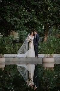 Bride and groom looking at each other as they stand by a pond in the gardens of Marie Gabrielle