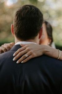 Bride rests her hand on the groom's shoulder, showing off her engagement ring