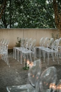 Set up of a wedding ceremony at Marie Gabrielle with clear acrylic ghost chairs within a grove of trees with string lights hanging and more lights wrapped around the base of each tree