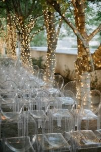 Set up of a wedding ceremony at Marie Gabrielle with clear acrylic ghost chairs within a grove of trees, with string lights hanging and more lights wrapped around the base of each tree