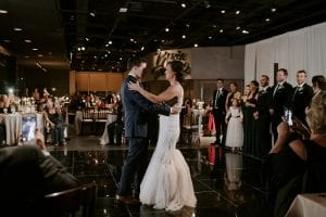 Bride and groom smiling at each other during their first dance at Marie Gabrielle, on a black dance floor as guests look on