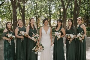 Bride and her bridesmaids wearing emerald green carrying their bouquets, smiling at the camera