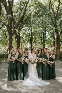 Bride and her bridesmaids wearing emerald green carrying their bouquets smiling at the camera