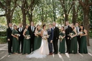 Bride, groom and their bridal party smiling at the camera in emerald green for the bridesmaids, and black suits for the groomsmen. Bridesmaids are holding their bouquets, and they are in the gardens of Marie Gabrielle