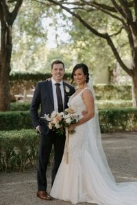 Bride and groom smiling at the camera while the bride carries her bouquet, standing in the gardens of Marie Gabrielle