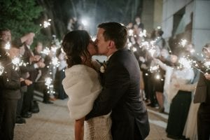 Bride wearing a white fur shawl kissing groom as guests stand in the background waving sparklers for the wedding exit