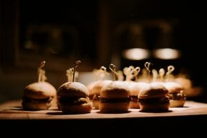 Sliders on display under a heat lamp, on a wooden board