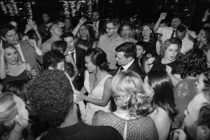 Bride and groom on their dance floor, surrounded by guests dancing and cheering