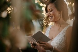 Bride smiling as she reads her vows at her wedding ceremony in the gardens of Marie Gabrielle