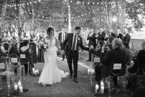 Bride and groom smiling as they exit their wedding ceremony while bridal party and guests look on, and the groom shakes the hand of a guest