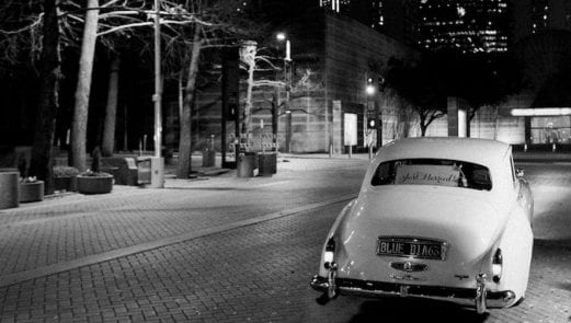 """White Rolls Royce with a """"Just Married"""" sign on the back, waiting in an empty cobbled street"""