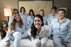 Bride and her bridesmaids smiling at the camera in their pajamas, sitting on a bed