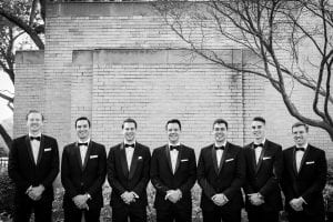 Groom and his groomsmen smiling at the camera with their hands crossed in front of them