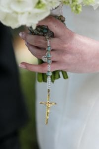 Closeup of the rosary that ties the bouquet together, with the brides hand holding it