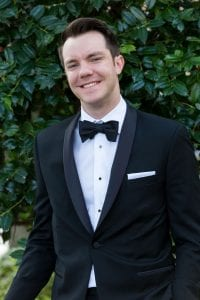 Smiling groom in a black tux looking at the camera