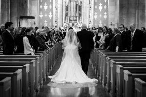 Bride and her father walking down the aisle to the altar, as guests look on smilingly