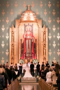 Bride, groom and their bridal party standing at the altar in front of the priest as guests look on. A large image of Christ is in the background