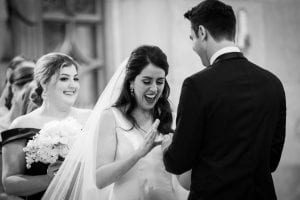 Bride smiles in delight as groom slips the wedding ring on her finger