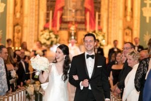 Bride and groom smiling and laughing as they leave the chapel and guests look on