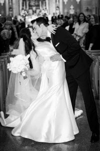 Bride and groom kissing as they exit the chapel, and guests look on