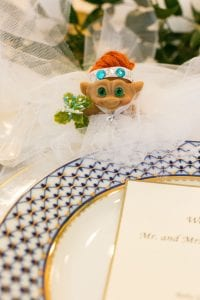 Closeup of a troll doll in lace tulle to depict a wedding dress, set by a blue and white dinner plate
