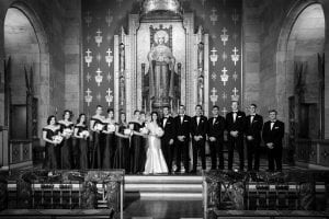 Bride, groom and their bridal party smiling in front of a picture of Christ at the church