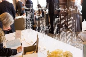 Guest signing the guestbook with acrylic seating charts as the backdrop
