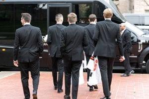 Groomsmen in black tuxes walking towards the transportation shuttle, holding jerseys in their hands