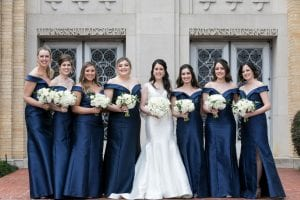 Smiling bride in a white wedding gown and her bridal party in off shoulder navy blue satin gowns standing in front of the church