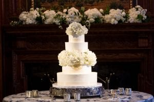 A white four tier wedding cake decorated with hydrangea and roses with a monogram on the second tier from the bottom