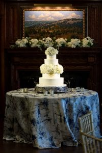 A white, four tier wedding cake decorated with hydrangea and roses, with a monogram on the second tier from the bottom, placed on top a patterned blue and silver linen on a round table