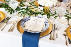Head table with charger plates, a patterned blue and white plate on top of a blue napkin, with a white menu card and centerpieces around