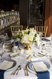Table with plateware serveware and glassware set with a white centerpiece blue napkins menus and patterned plates for the dinner reception