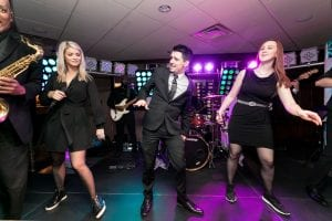 The wedding band and singers performing a synchronized dance while they sing