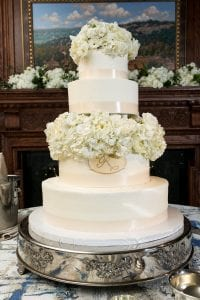 A white, four tier wedding cake decorated with hydrangea and roses, with a monogram on the second tier from the bottom
