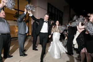 Bride and groom waving laughing and waving goodbye as guests wave silver pom poms for their exit