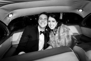 Bride and groom smiling at the camera as they are in their getaway car, ready to drive off